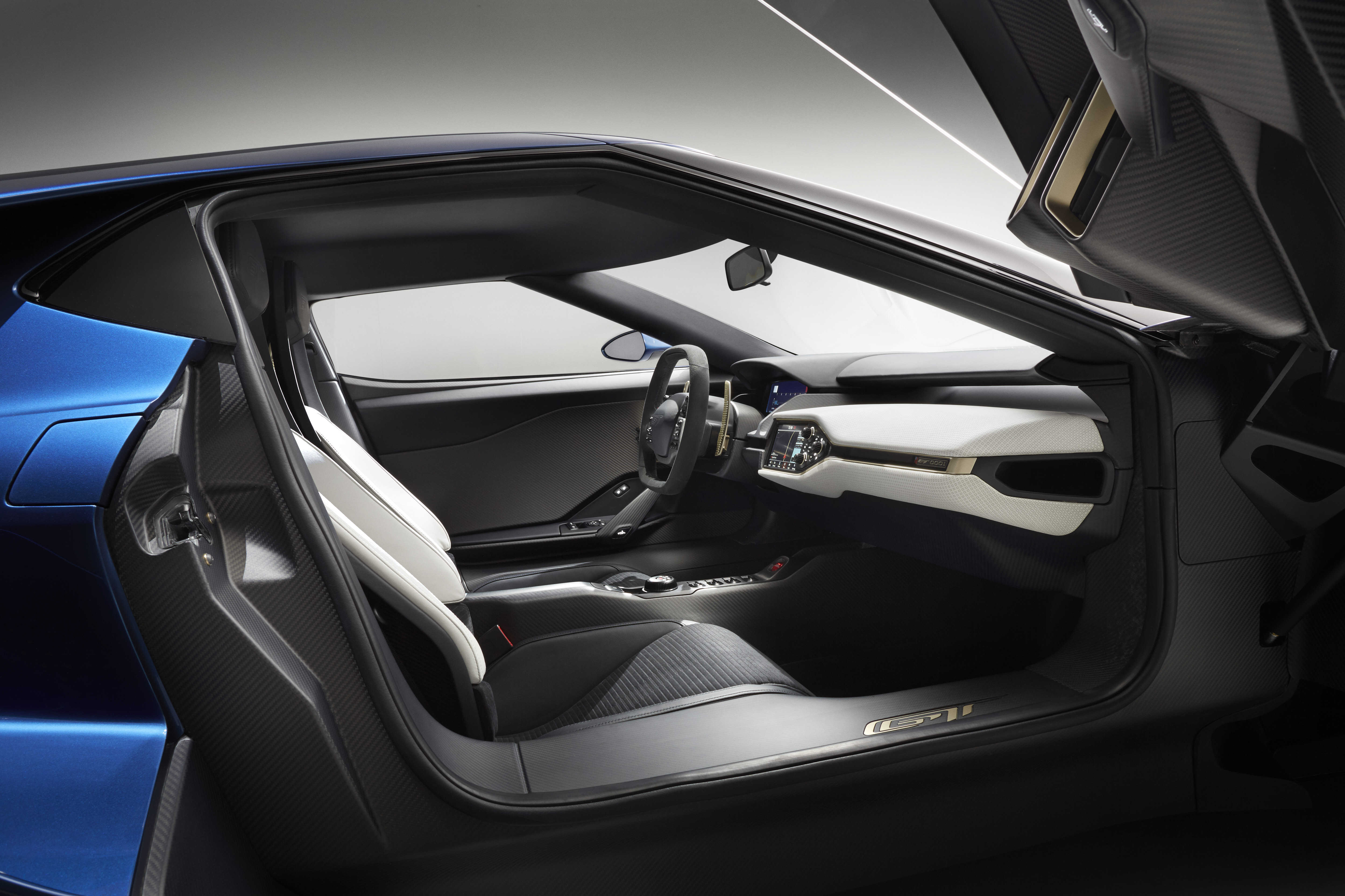 The purposeful interior on the all-new, two-seat, carbon-fiber, mid-engined Ford GT supercar is accessed by upward-swinging doors.