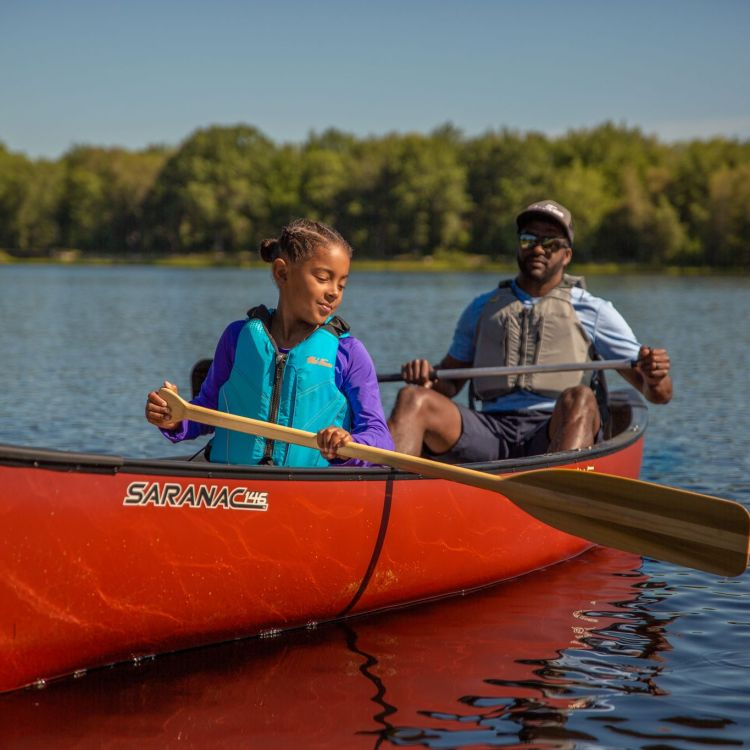 A young girl and man paddle in a red canoe.