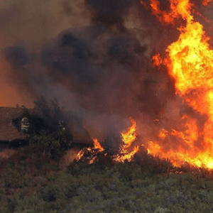 Wildfire burns near a home in California