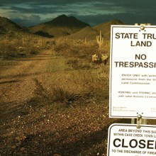 "A sign states ""State Trust Land, No Trespassing"" along a road in Arizona."
