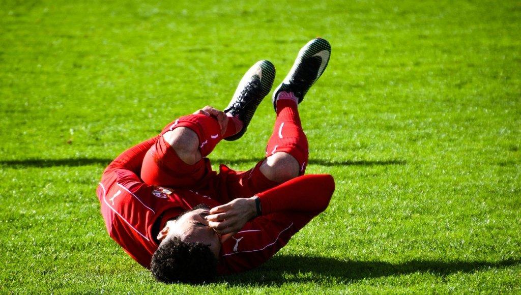 마그네슘 부족 시 근육 경련, 떨림, 쥐가 발생하는데 쥐가 나고 있는 축구 선수 사진.