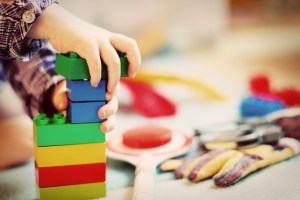 Child playing with large lego blocks or duplo with only hand visible