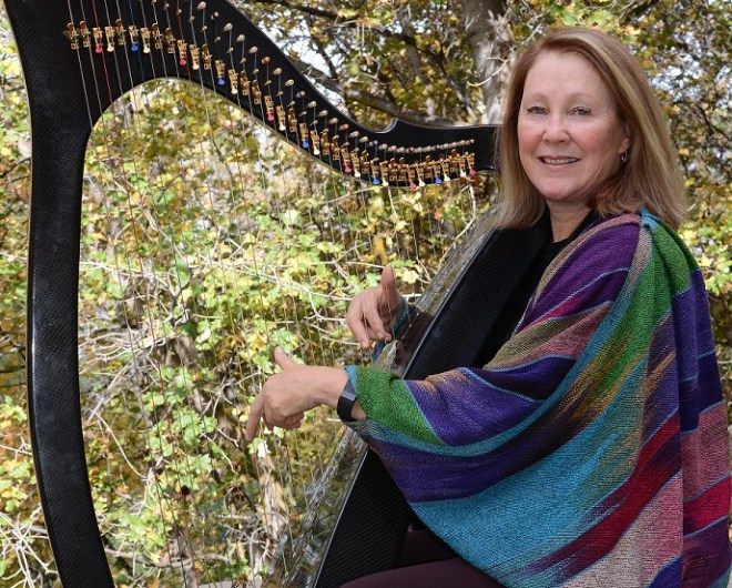 Therapeutic Harpist playing carbon fiber harp outdoors