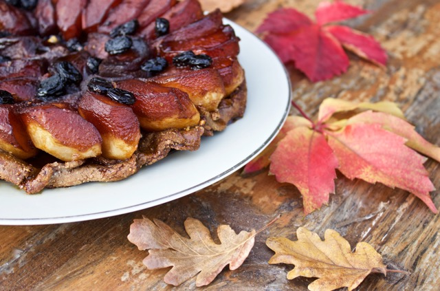 Thanksgiving apple tarte, side shot, on a white plate on a wooden background surrounded by fall leaves