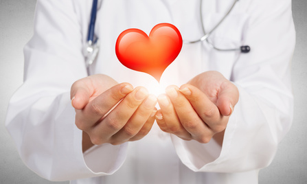 Close view of female doctor holding with care red heart
