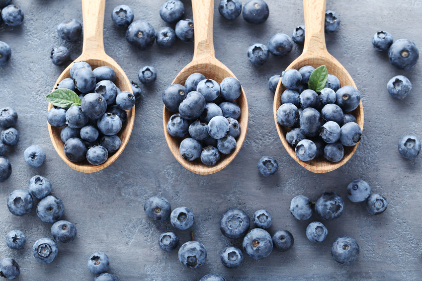 Ripe and tasty blueberries on grey wooden table