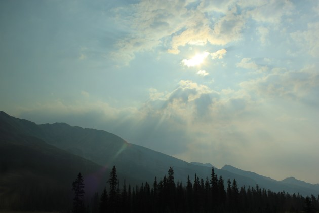 Sun shining through the clouds over mountains