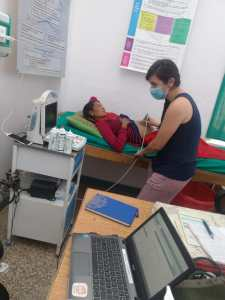 Person performs ultrasound test on someone lying on a bed, her shirt slightly lifted to allow for the test.