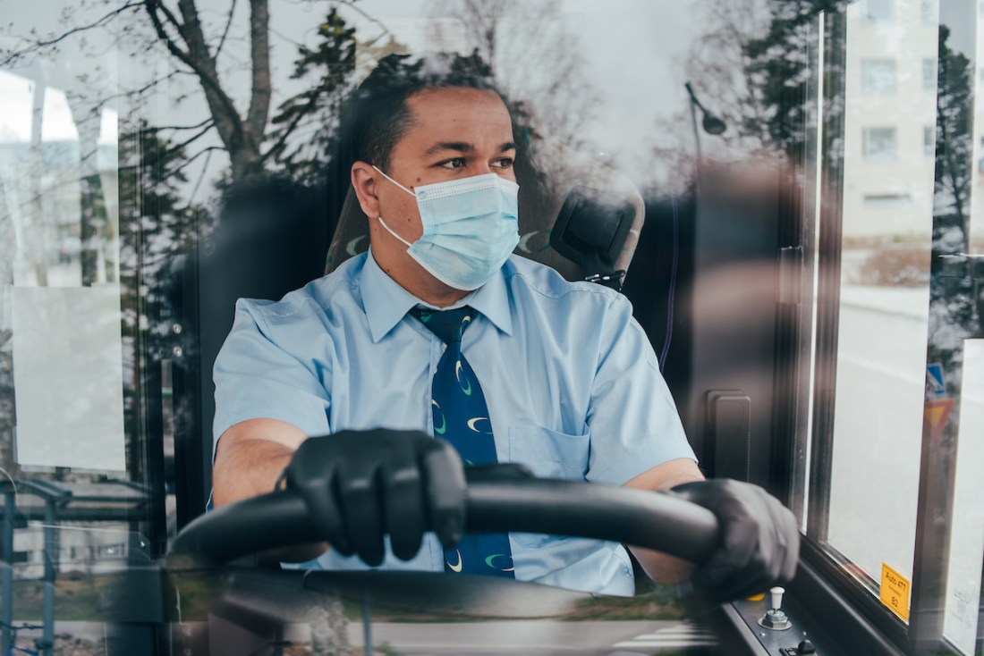 Man wearing a mask while driving a bus