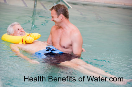 Elder person being helped by a water therapy specialist