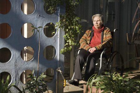 elderly woman suffering from arthritis sitting in a wheelchair