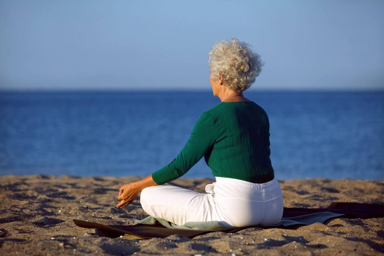 senior woman doing yoga meditation beach