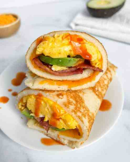 Pancake wrap with crispy bacon, soft scrammed eggs, melted cheese, hot sauce, and creamy avocado. Best healthy breakfast ever!