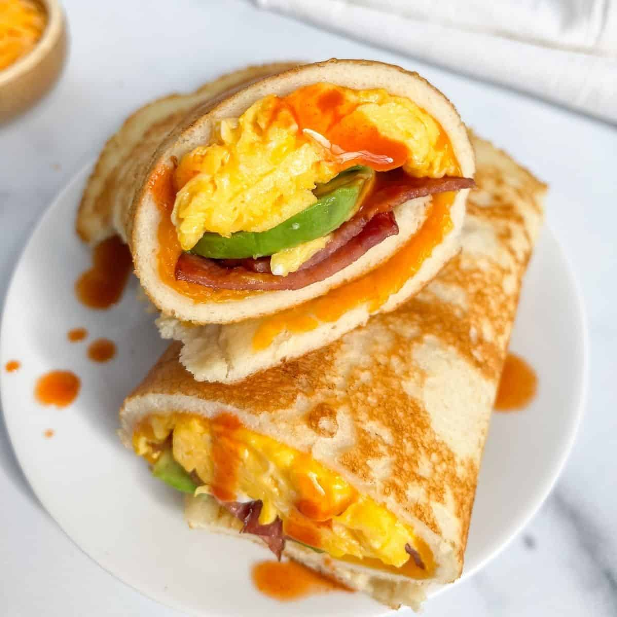 Healthy bacon, egg and cheese pancake burrito with avocado. Such an easy, tasty and fun breakfast sandwich made with clean ingredients. Recipe by Healthful Blondie.