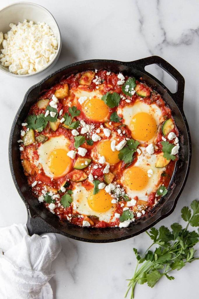 Best healthy shakshuka recipe with sunny side up eggs, fresh tomatoes, zucchini and crumbled feta.