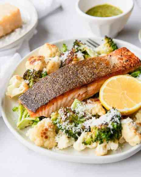 Crispy Salmon with parmesan roasted cauliflower and broccoli. The perfect healthy salmon bowl dinner or lunch. Also ideal for families and meal prep! Recipe by Healthful Blondie.