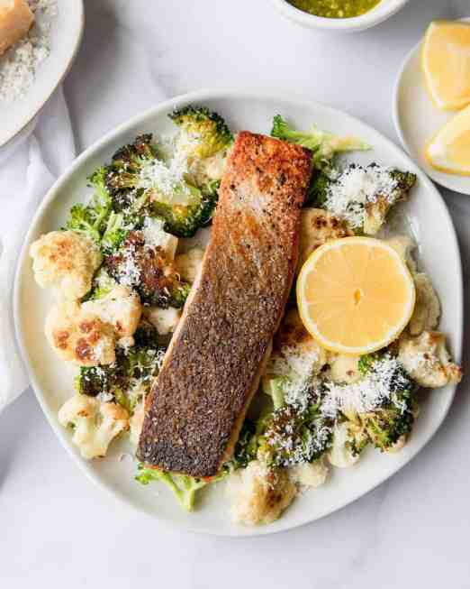 Cheesy, tender and crisp broccoli and cauliflower with flakey salmon. The perfect easy dinner for families, athletes and fitness lovers. Recipe by Healthful Blondie & Tati Chermayeff.