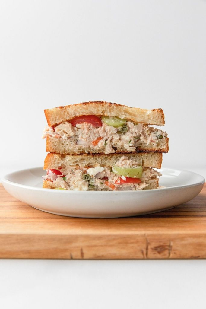 Greek tuna feta melt sandwich stacked on top of each other with toasted healthy bread.