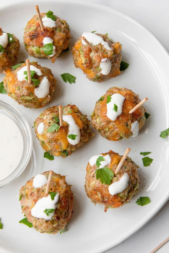 Healthy broccoli cheddar turkey meatball poppers with ranch dressing drizzled on top.