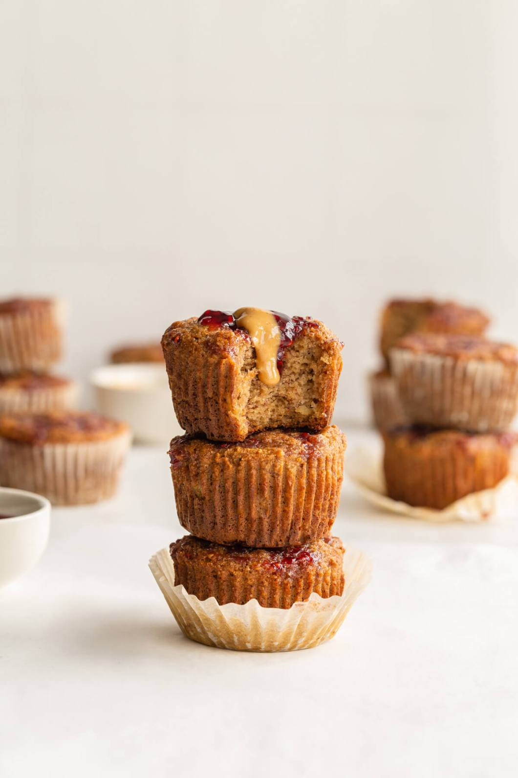 Stack of three banana muffins with a peanut butter and jelly drip