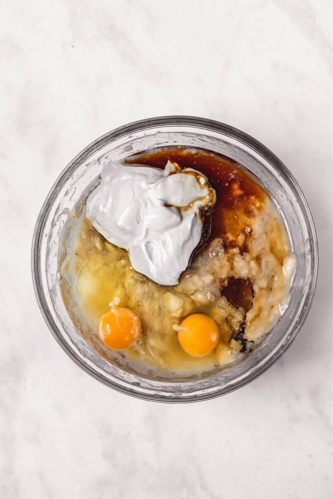 whisking together banana, eggs, and greek yogurt to make moist banana bread