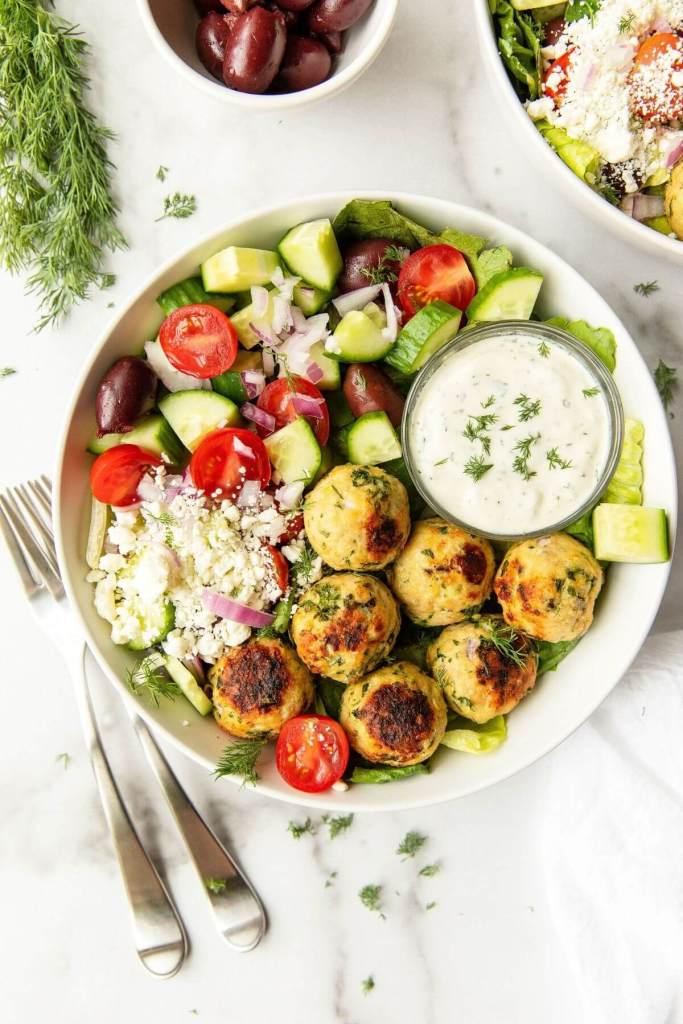 best ever juicy greek meatballs served with Mediterranean salad, feta cheese, and tzatziki