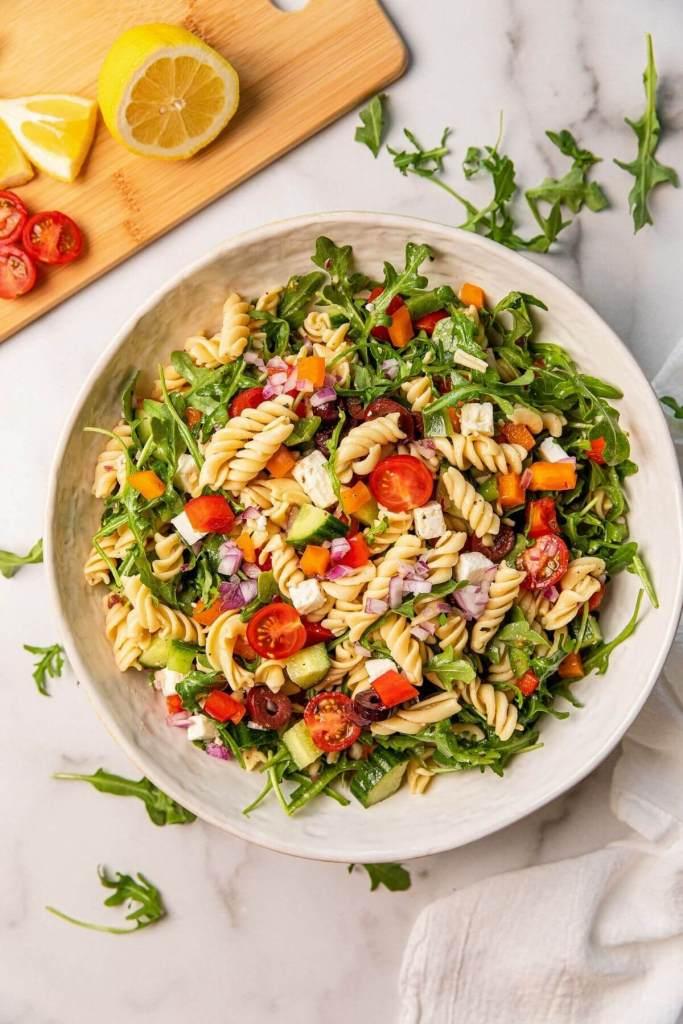 healthy Mediterranean Greek chickpea pasta salad in large white serving bowl
