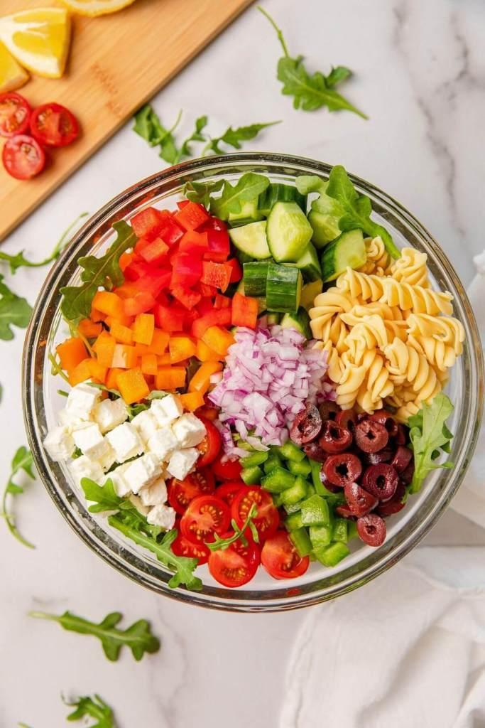 Ingreditents in Greek pasta salad in glass mixing bowl