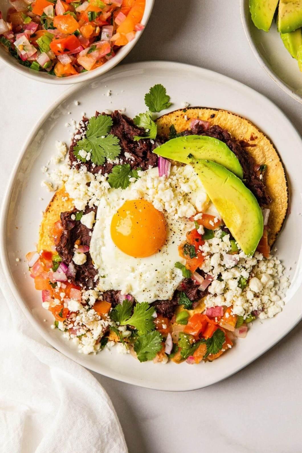 Best huevos rancheros with sunny side up egg on corn tortilla