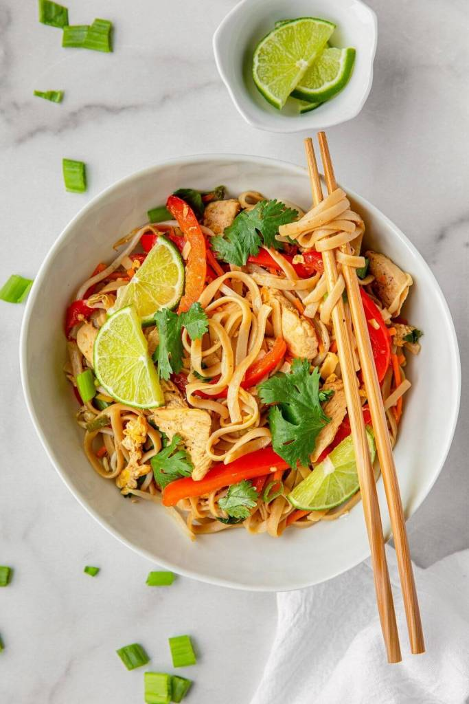healthy chicken pad thai in a bowl with chop sticks