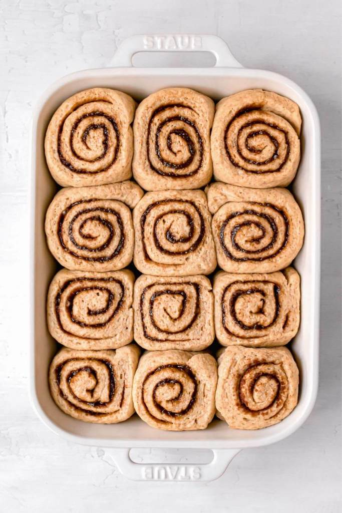 healthier cinnamon roll in a baking dish after second proof