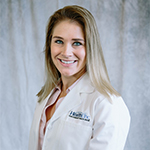 Clinical Pharmacist Lynn Thoma wearing a HealthLinc overcoat and pink button-up shirt
