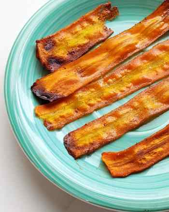 Slices of vegan bacon made from carrots on a teal plate.