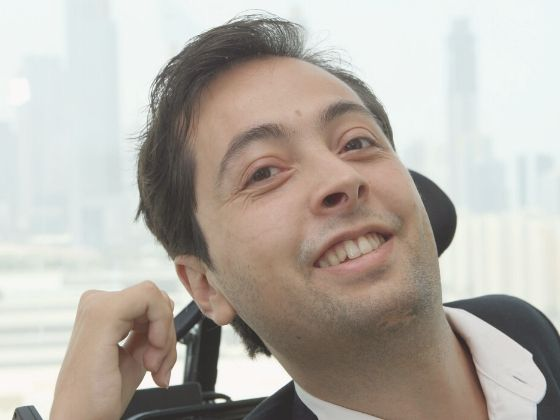Dr. Pineda in a wheelchair, smiling