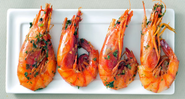 closeup of a plate with spanish shrimps cooked with garlic and p
