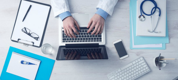 doctor with computer and cell phone 600x271