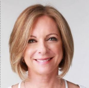 Headshot style photo of Dr. Alison Deliman, wearing short blonde bob and smiling against white background.