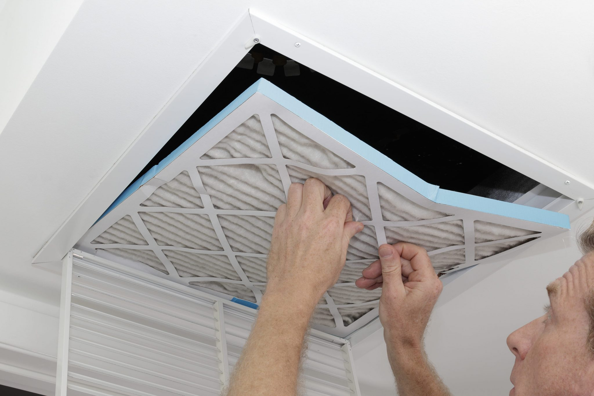 Person removing an old dirty air filter from a ceiling intake vent of a home HVAC system to improve indoor air quality.