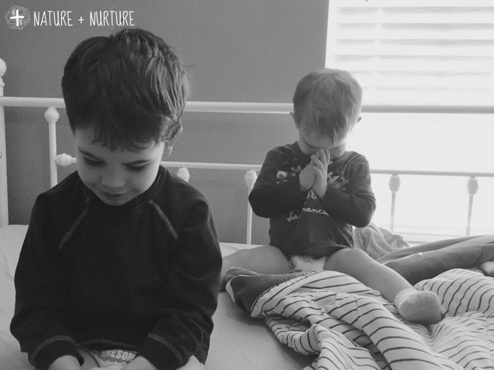 Bible study for kids during prayer time. Black and white photo of two little boys bowing their heads to pray.