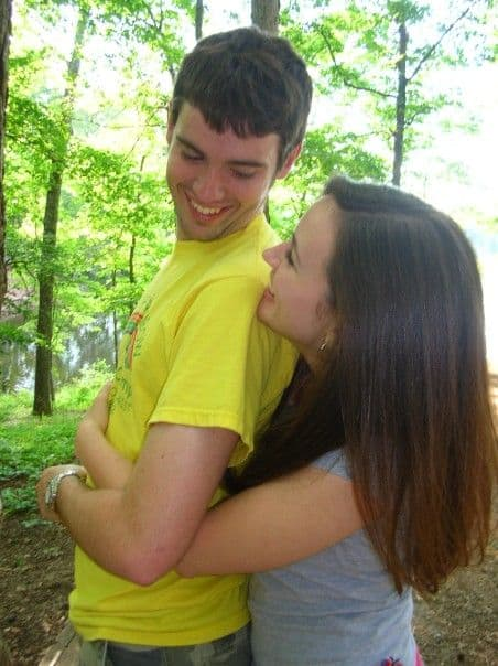 A young man and woman hugging in a green forest.