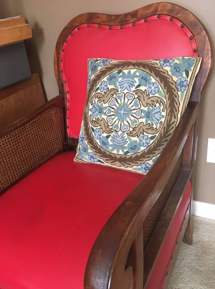 An antique red leather chair with decorative pillow.
