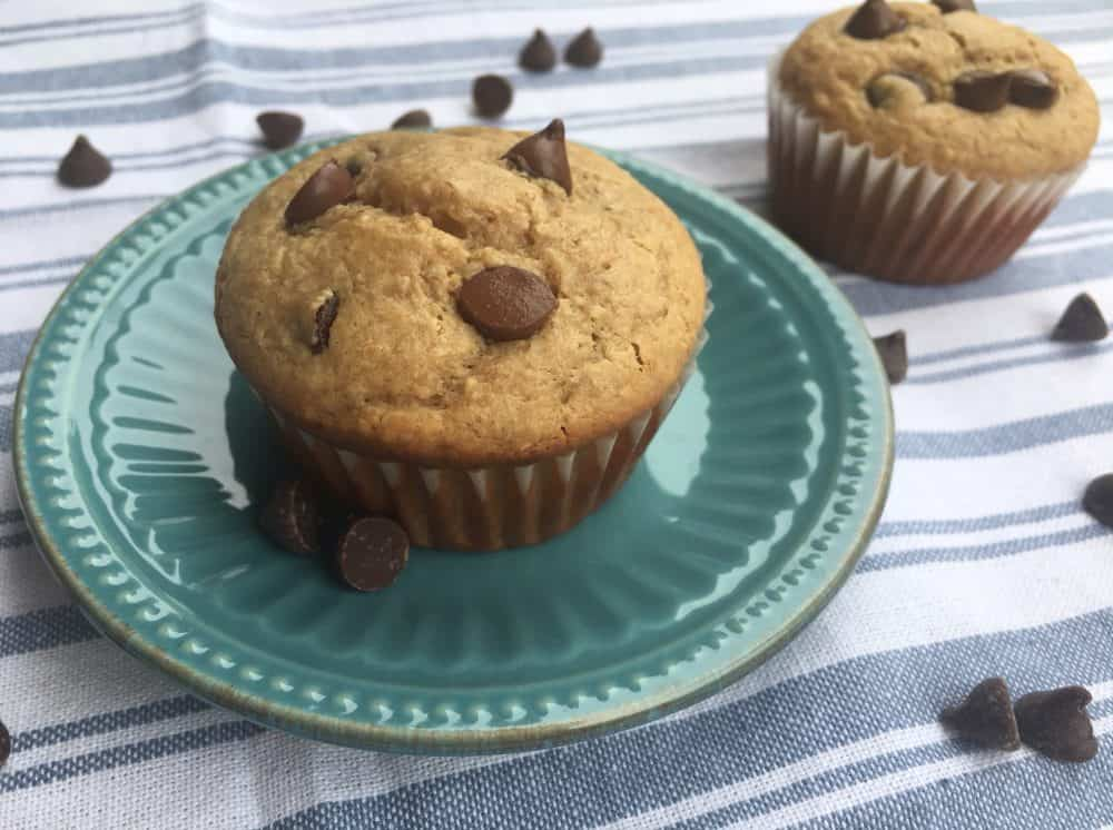 Chocolate chip peanut butter breakfast muffins on an antique blue plate with chocolate chips and another muffin in the background.