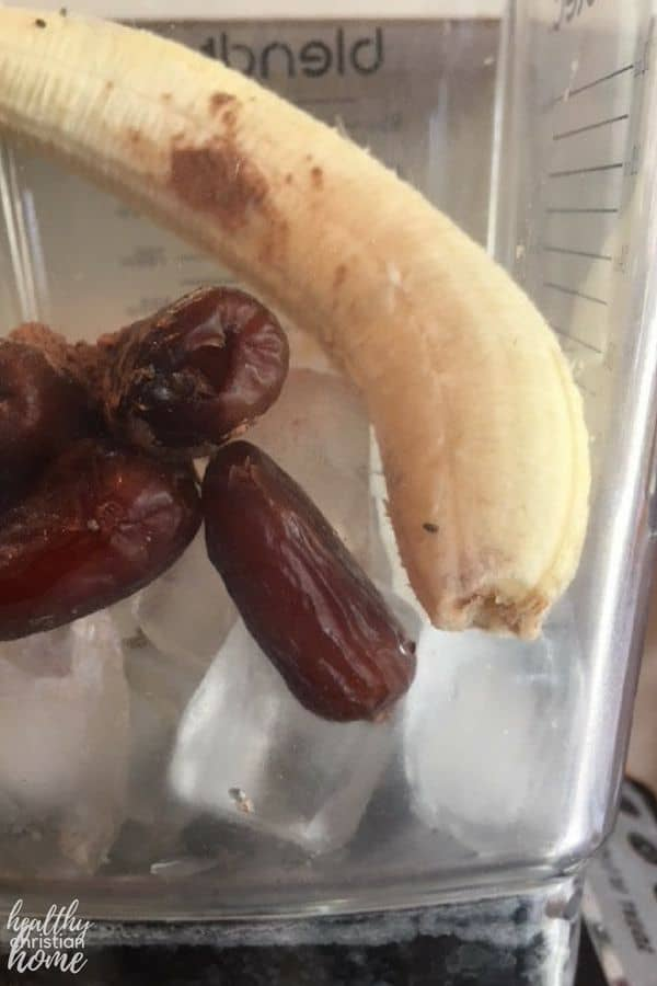 Healthy chocolate smoothie ingredients in a blender, including a banana, ice, and dates.