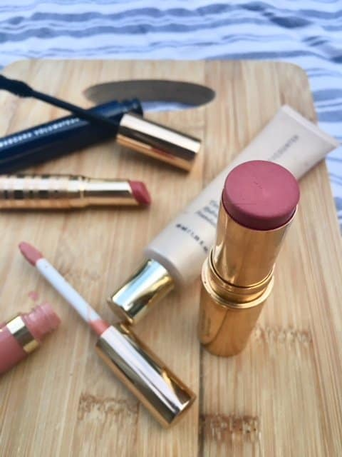 Everyday natural makeup including blush, lipstick, and mascara on a wooden surface.