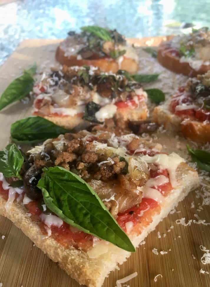 Homemade mini pizzas on a wooden board garnished with fresh basil.