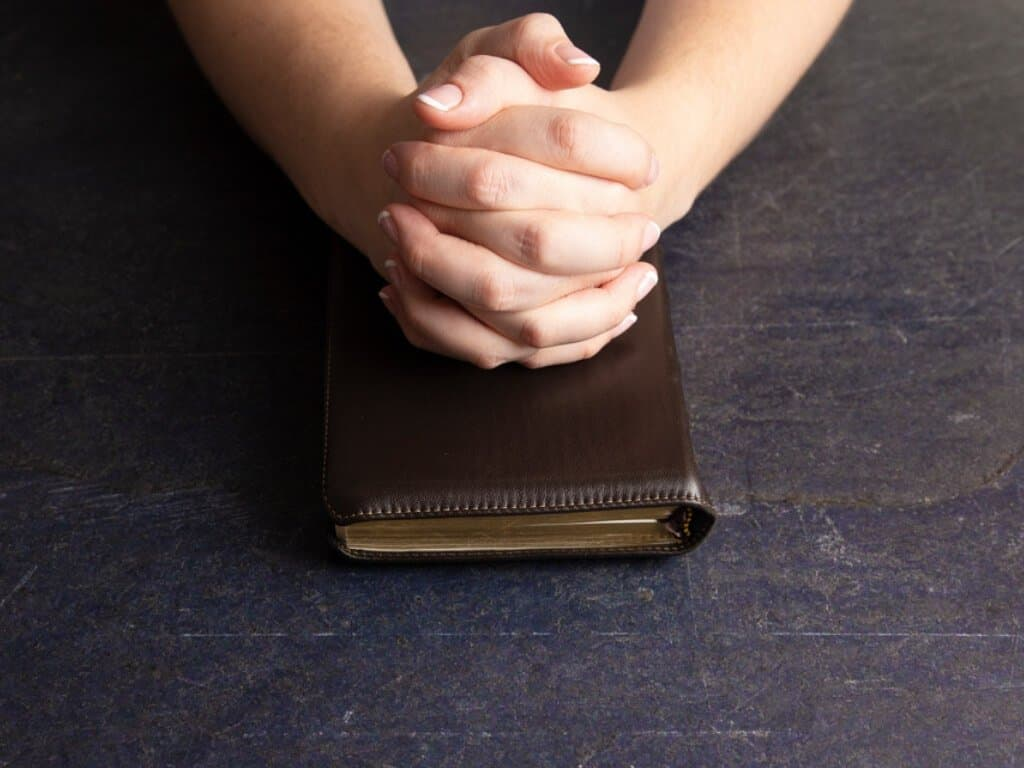 Hands folded in prayer on top of a prayer journal.