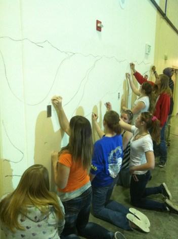 mural kneeling and painting
