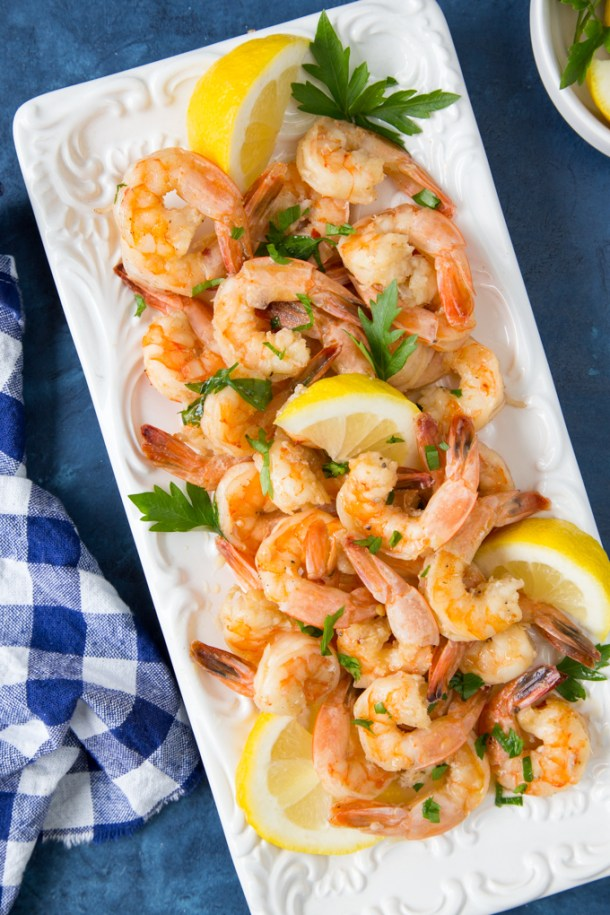 Shrimp Scampi {Low Carb, Keto}- cooked shrimp scampi on a white platter with fresh lemon and parsley