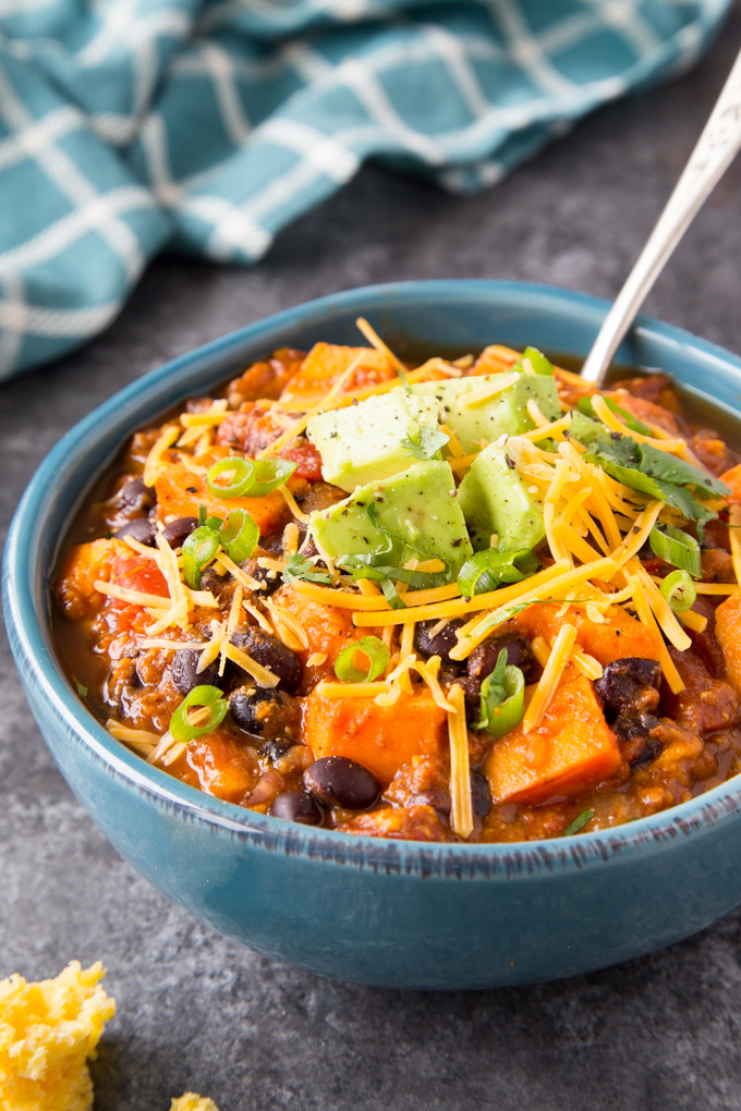 A close up view of Sweet Potato and Black Bean Chili with diced avocado, shredded cheese and a sprinkle of green onions in a blue bowl