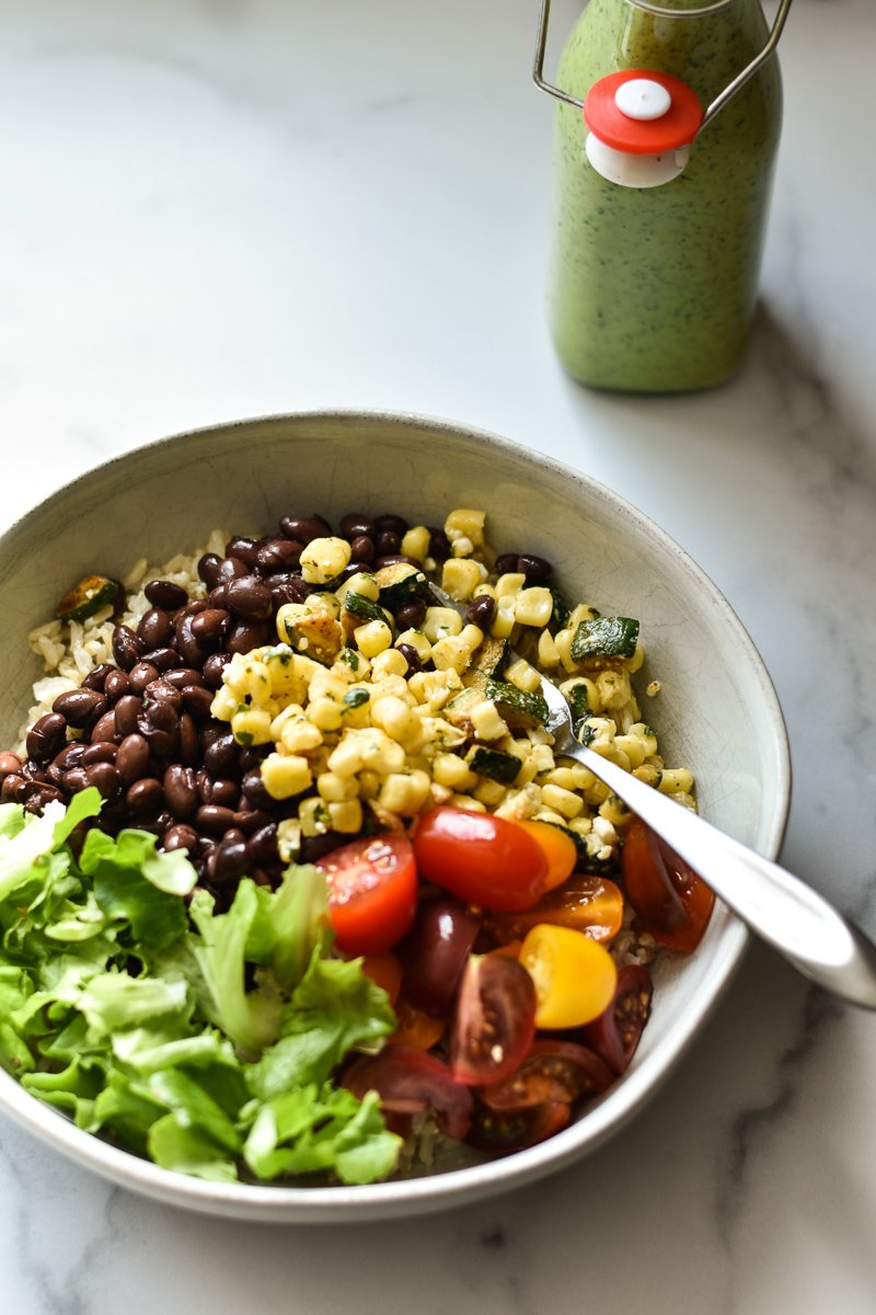 vegetarian burrito bowl with a bottle of green goddess dressing